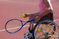 Photo of person in a wheelchair playing tennis